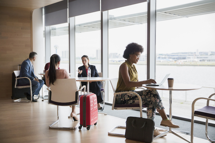 business travellers working in lounge - frequent flyer points - flight centre business travel