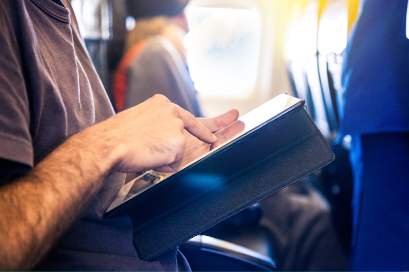A man using a tablet on a plane
