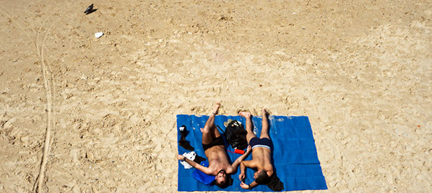 Honeymooning couple relaxing on the beach