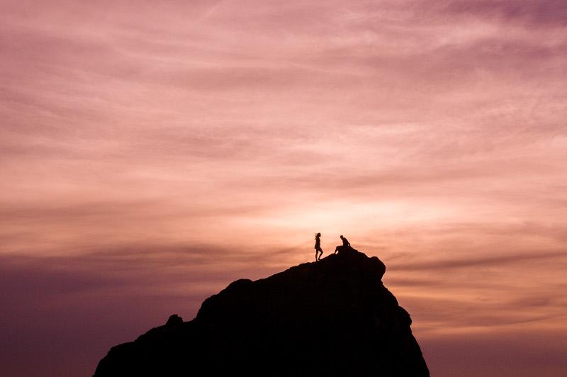 man and woman climbing rock as sunset