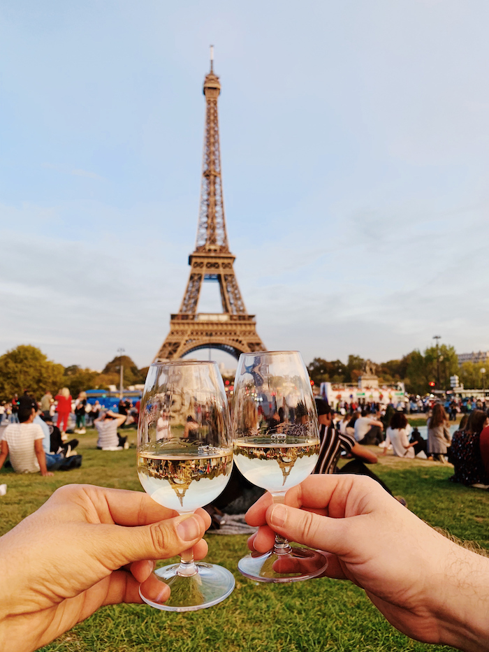 a couple toast champagne glasses in front of the Eiffel Tower in Paris - 14 romantic travel experiences for valentines day
