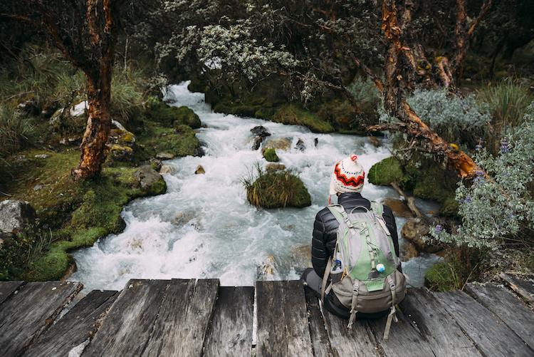 Hiker resting by stream in Peru