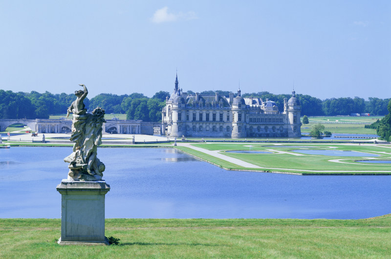 chantilly castle from afar with statue in foreground