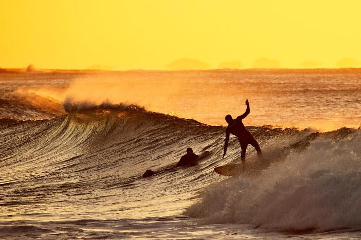 surfer riding wave newcastle nsw at sunrise