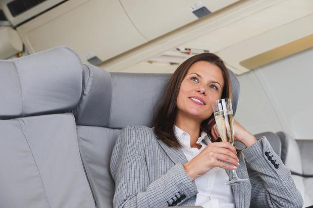 Woman drinks champagne on flight