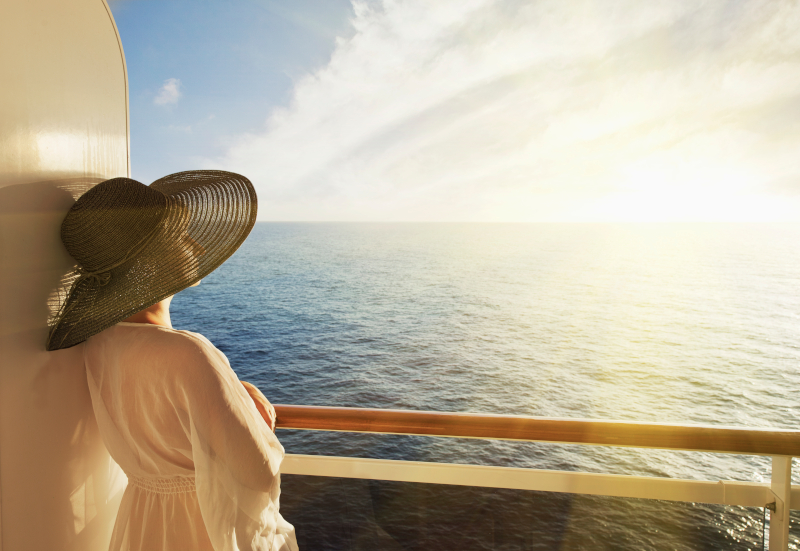 woman looking out to sea from her cabin. She is wearing a black hat