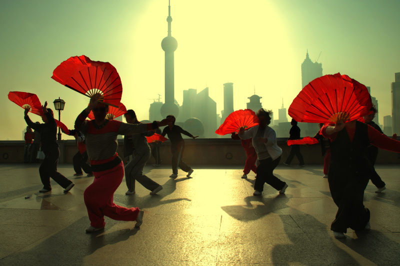 Woman do a fan dance on the Bund in Shanghai, China
