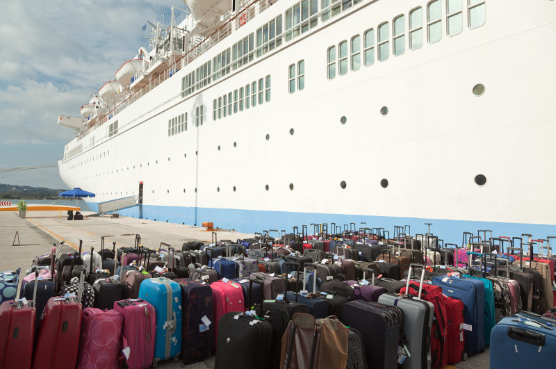 suitcases lined up on dock in front of cruise ship