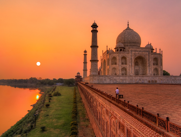 a man watches the sunrise over the taj mahal in Agra - romantic travel experiences for valentines day