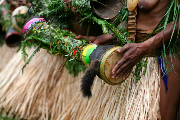 papua new guinea tribesman playing drum