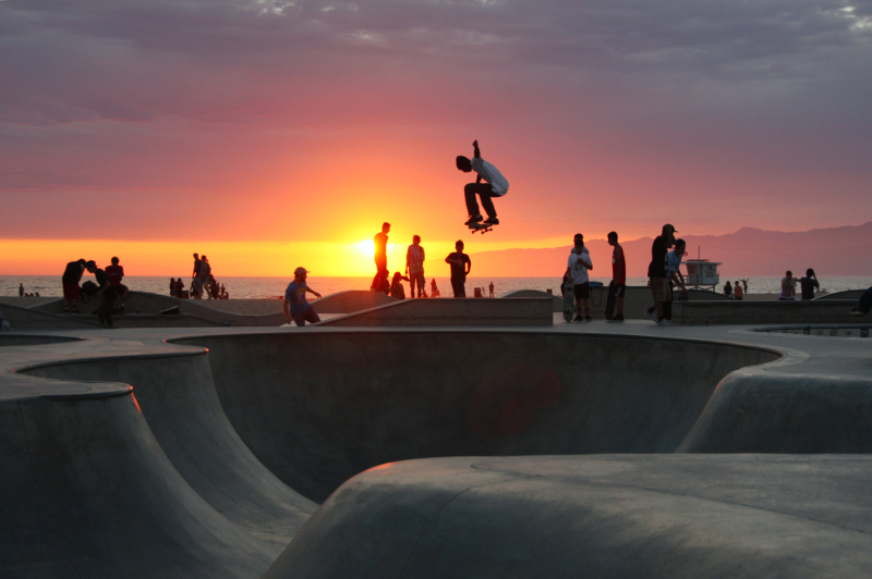 boys ride their skateboards at Venice Beach, California, at sunset