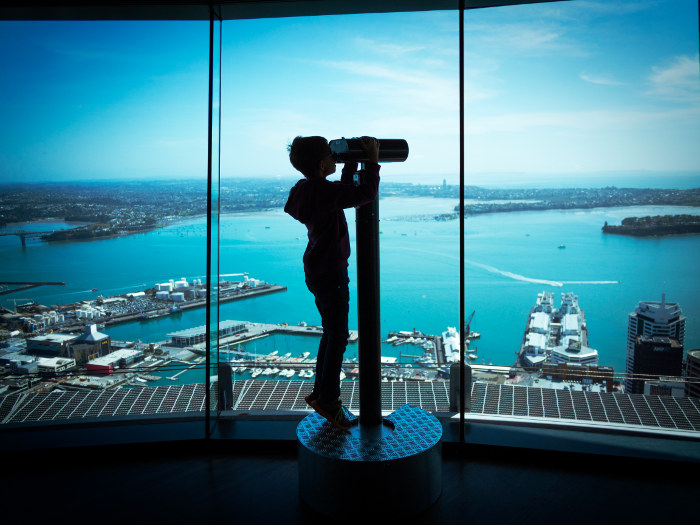 young boy looking through binoculars at auckland skytower