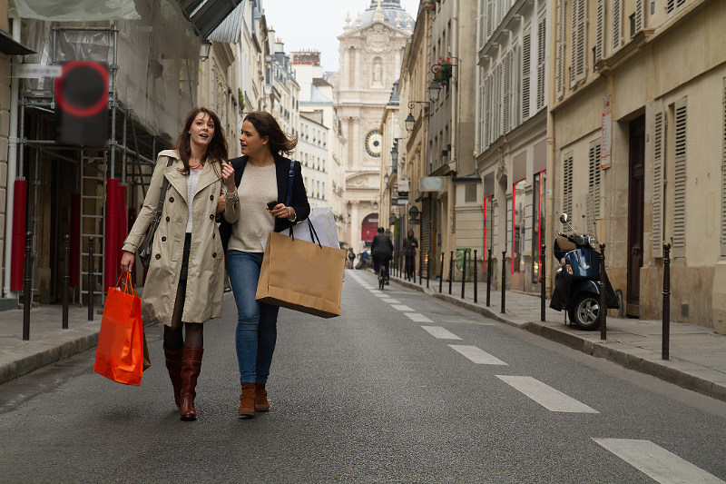 Two women walking down a street in Paris with shopping bags