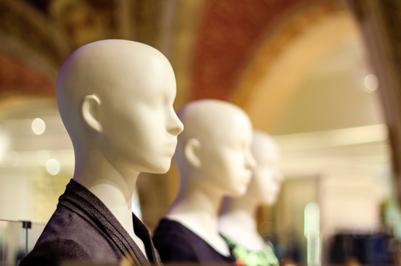 Mannequins inside a fashion store stare blankly ahead