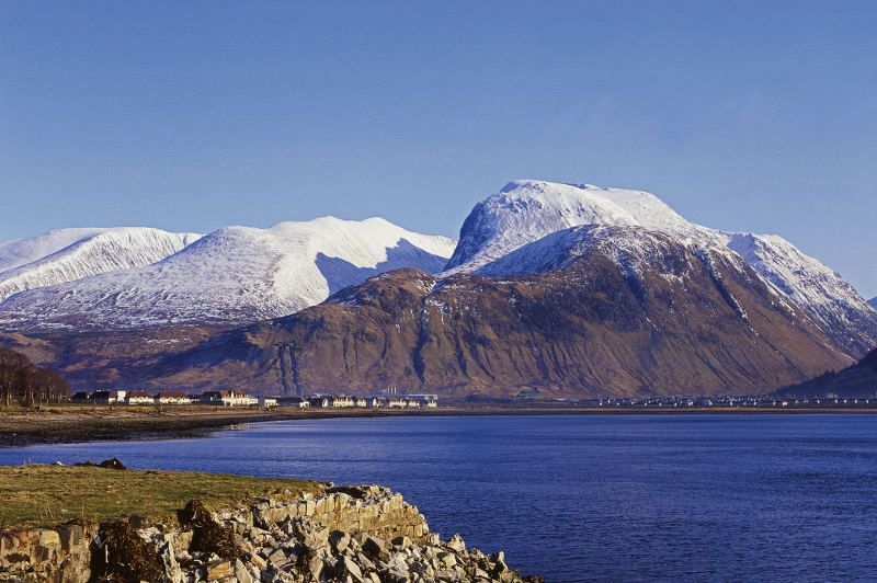 ben nevis covered in snow behind lake
