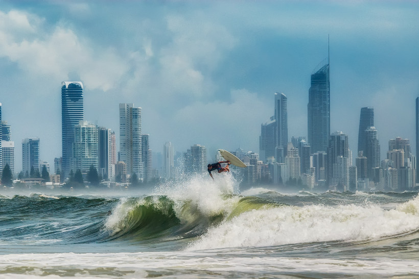 burleigh heads surfer on wave with skyline behind