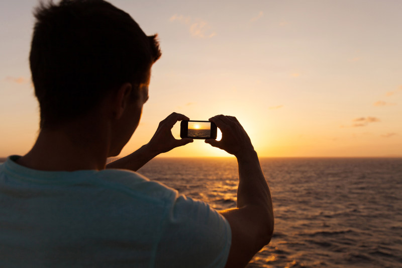 man taking photo of sunset on Smartphone from cruise ship deck