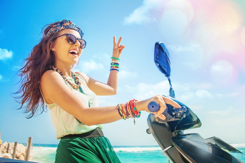 A woman riding a motorbike along beach that should be wearing a helmet!