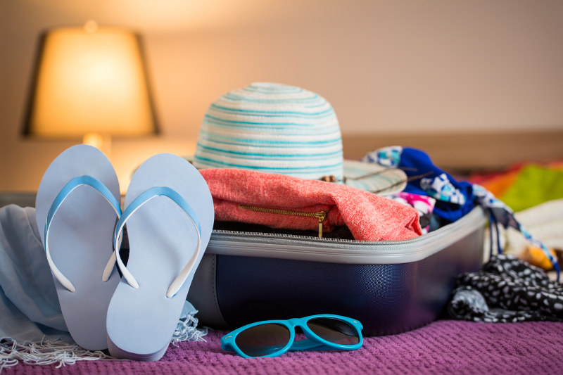 suitcase open in cruise ship cabin with hat, thongs spilling out