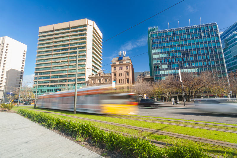 tram moving fast past modern buildings in adelaide