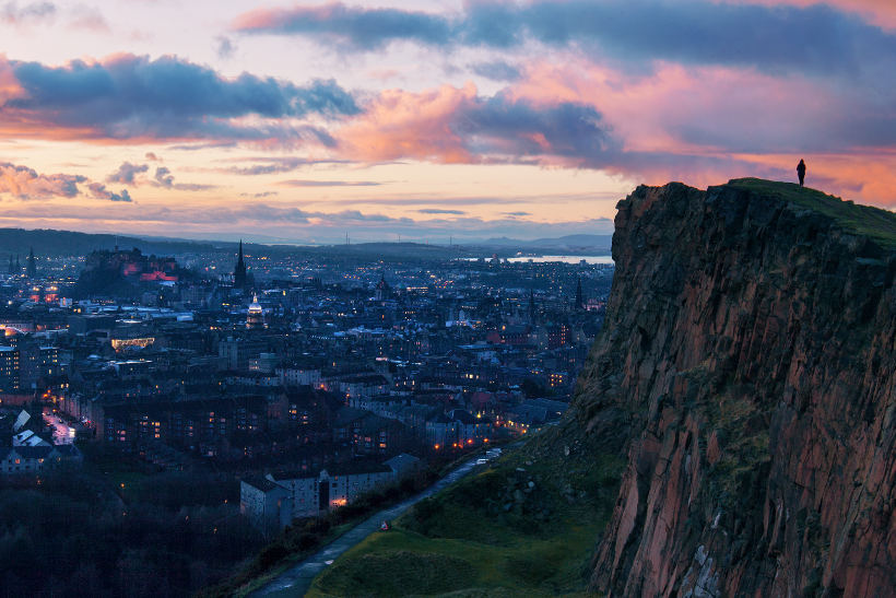 man ontop of arthurs peak overlooking edinburgh at sunset
