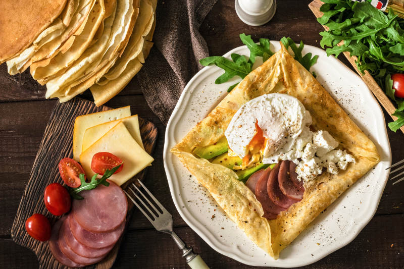 savoury crepe with ham, egg, cheese and sides on plate