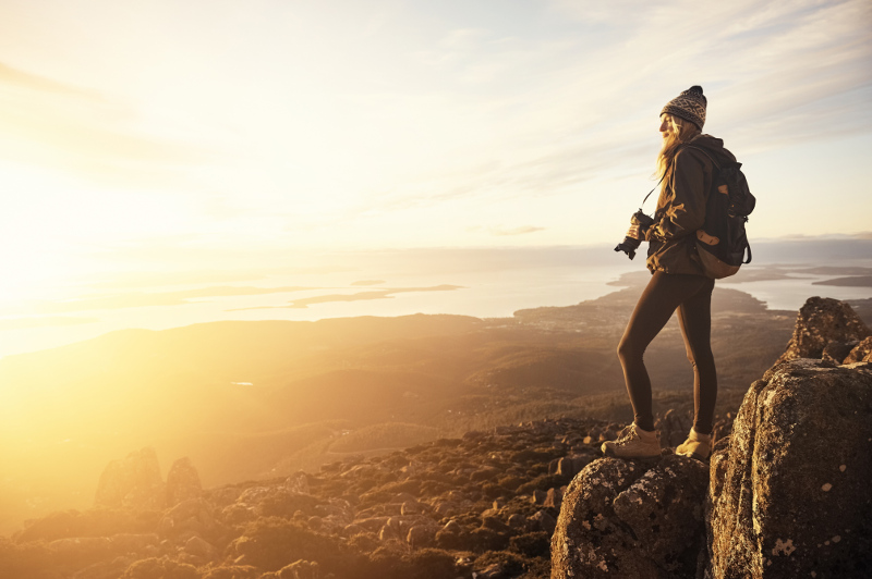 Woman with camera on mountain top