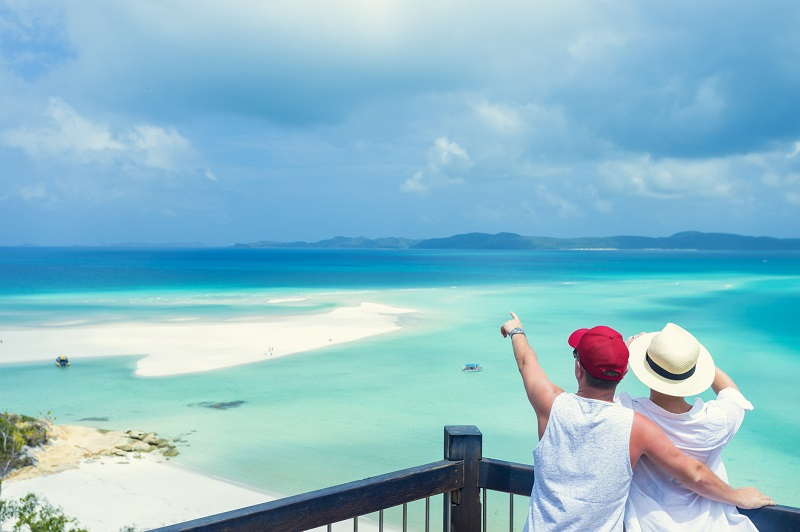 Couple looking at the view of Whitehaven beach. Whitehaven beach is in the Whitsunday islands in Queensland, Australia.