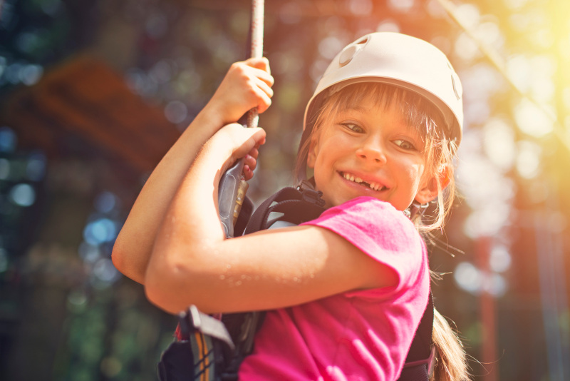 Young girl smiling on zip line