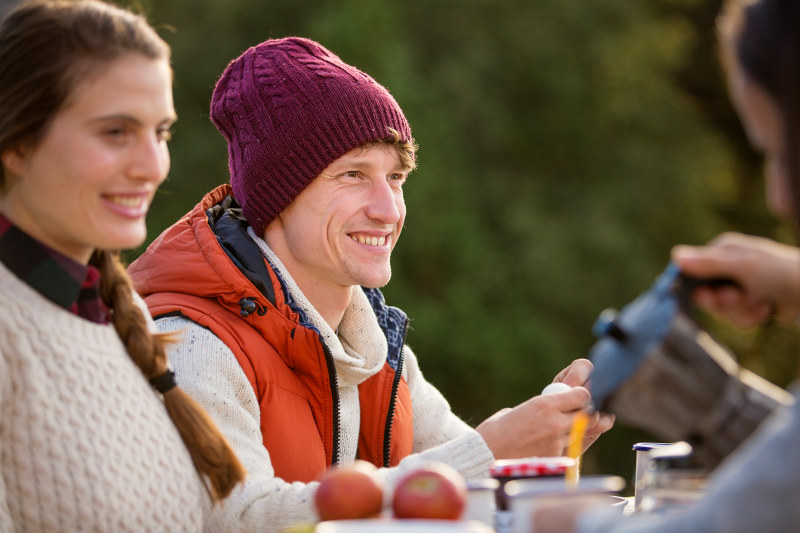 man wearing beanie at table with friends