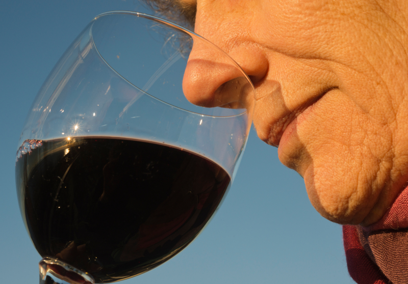 A close up of a man smelling a red wine