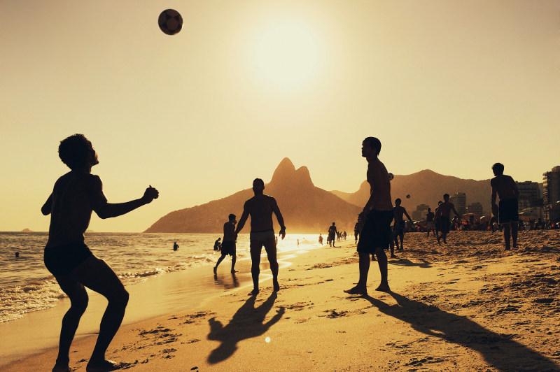 men playing football on Ipanema beach, rio de janeiro, brazil