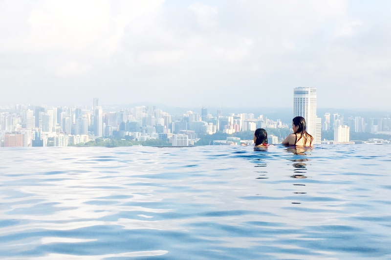 Two women in infinity pool overlooking Singapore