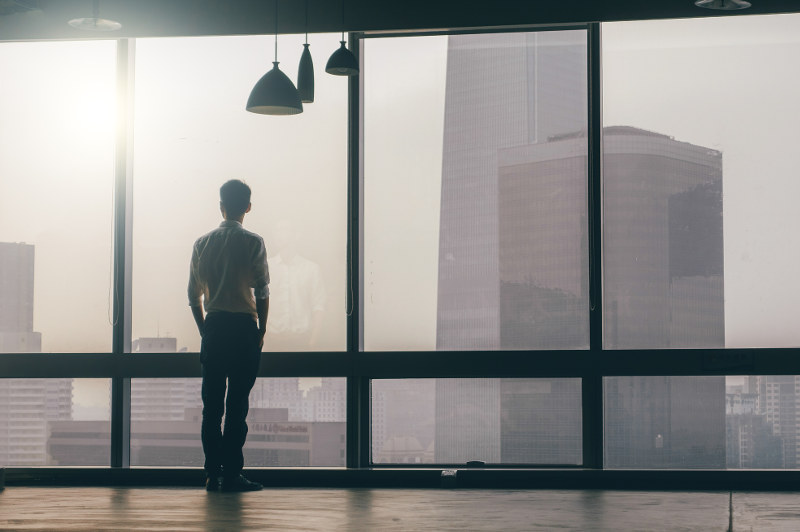 man looking out office window over city
