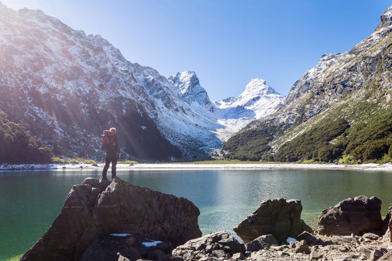 man standing on rock infront of lake and snow capped mountains