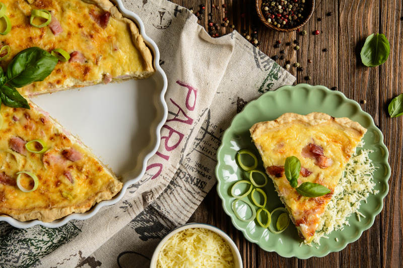 quiche lorraine in pan from above with slice on separate plate.