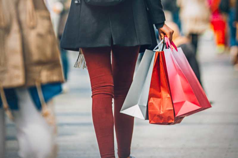 View of woman's legs and several shopping bags that she is carrying