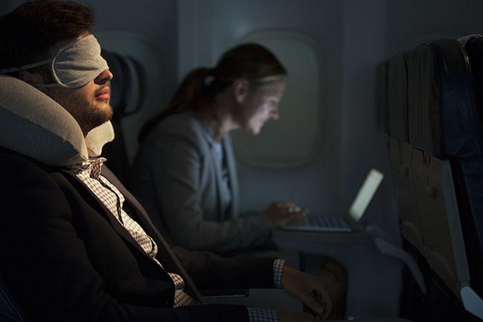 business man sleeping with eye mask on plane