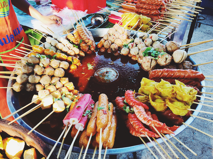 a selection of street food on a burner in a Thai market