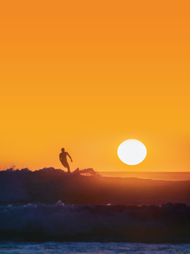 surfer on wave with sun setting behind