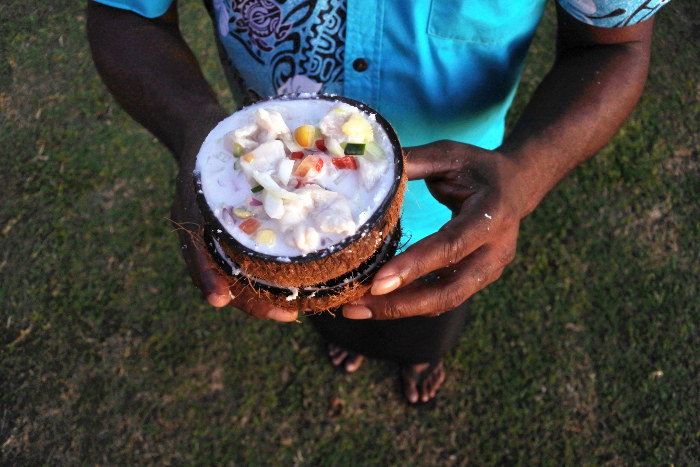 fijian man holding fish salad in coconut