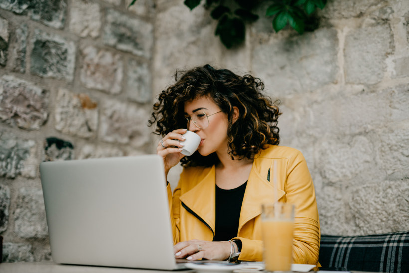 woman working on computer drinking coffee