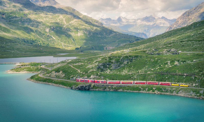 The Bernina Express train travelling on the Bernina Pass. The lake water is a stunning blue colour