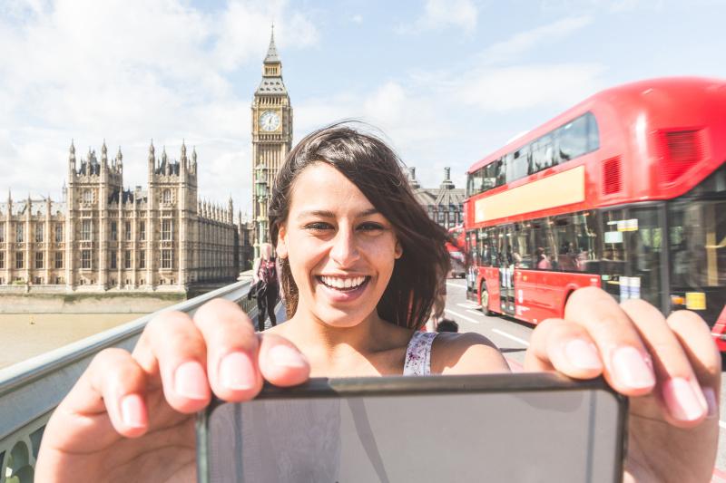 Woman taking selfie on bridge in London, United Kingdom