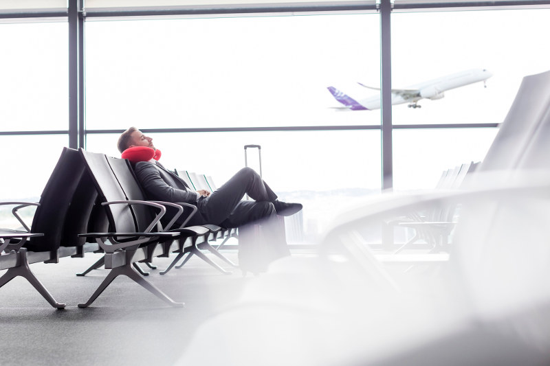 man sitting with travel pillow in airport lounge