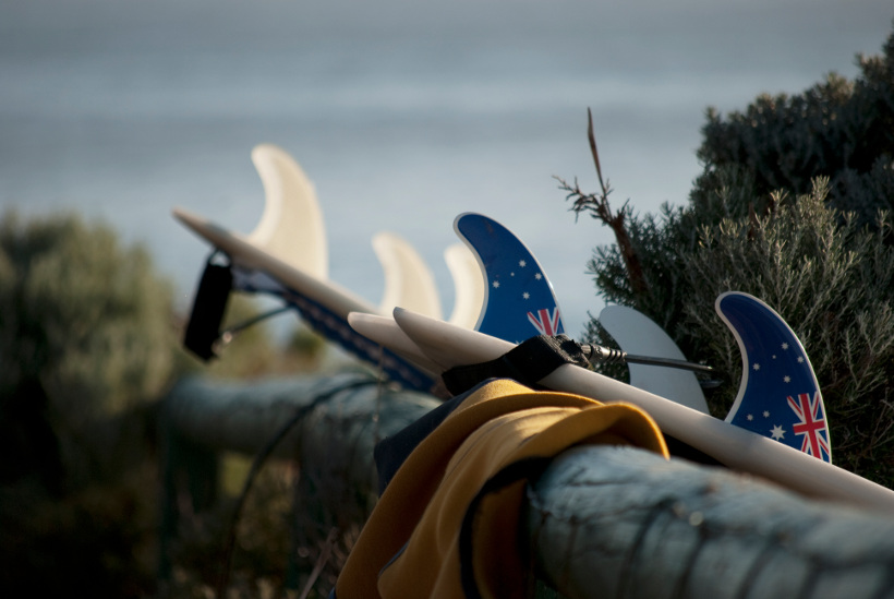 surfboards leaning against fence