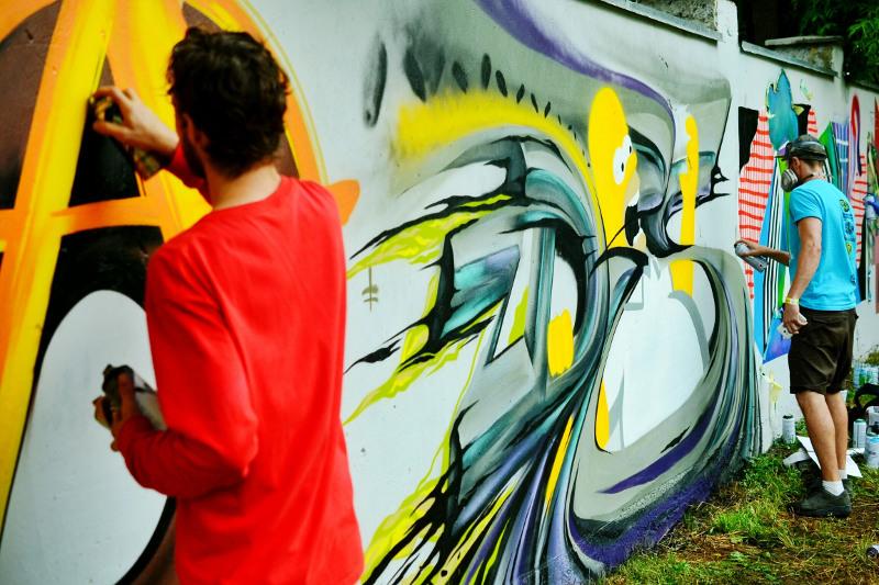 Two men create a graffiti wall mural