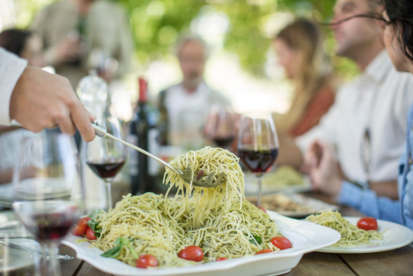 table of people with red wine glasses and someone serving pesto pasta