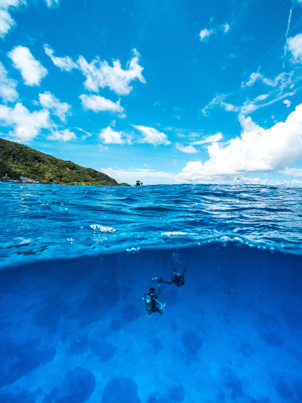 divers under water with view of ocean and mountains above