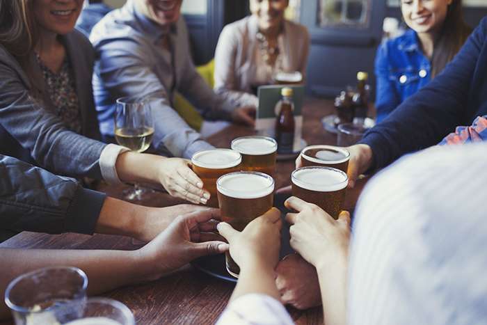 group of mates cheersing beer in british pub